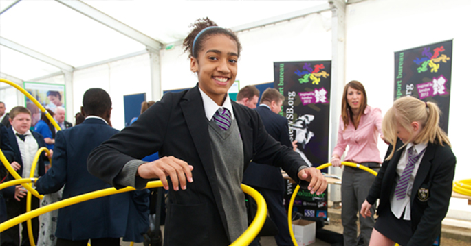 Secondary school girl smiling participating in hoop exercise